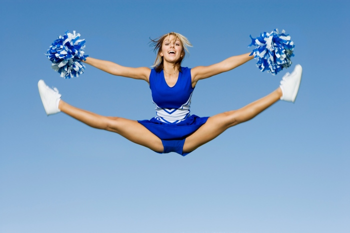 Cheerleader With Pompoms Doing Splits Against Sky